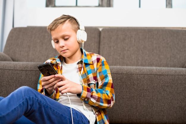 Jongen met een koptelefoon met behulp van smartphone