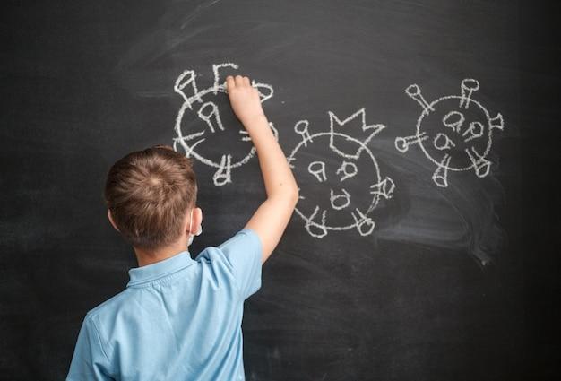 Jongen met een medisch masker tekent een coronavirus op een schoolbord