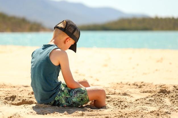 Jongen met een pet die op het strand zit te spelen in het zand