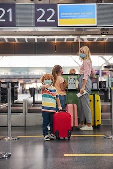 Jongen met een rollende koffer die duim omhoog geeft