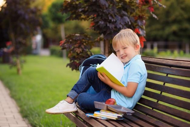 Jongen met een rugzak en boeken op de eerste schooldag zit in het park.