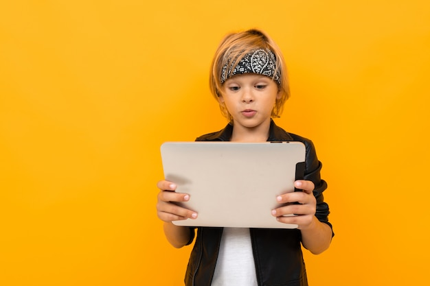 Jongen met een tablet op geel