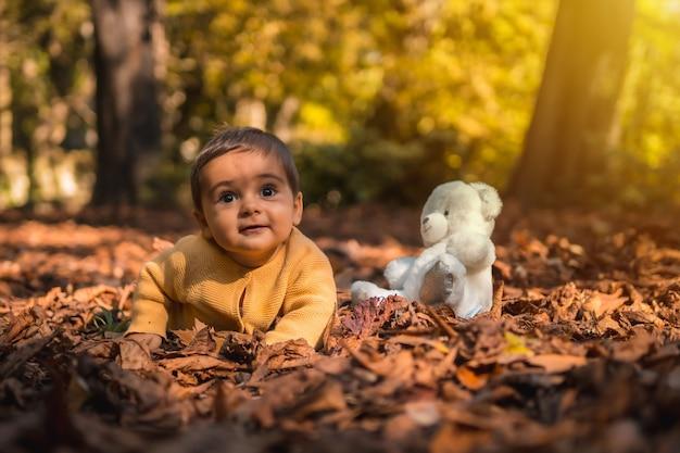 Jongen met een witte teddybeer in het park op een herfstzonsondergang. natuurlijk licht, baby halverwege het jaar geniet van de natuur