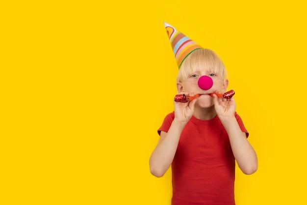 Jongen met feestmuts en rode clownneus die fluitje vasthoudt. portret op gele achtergrond. matineevakantie.