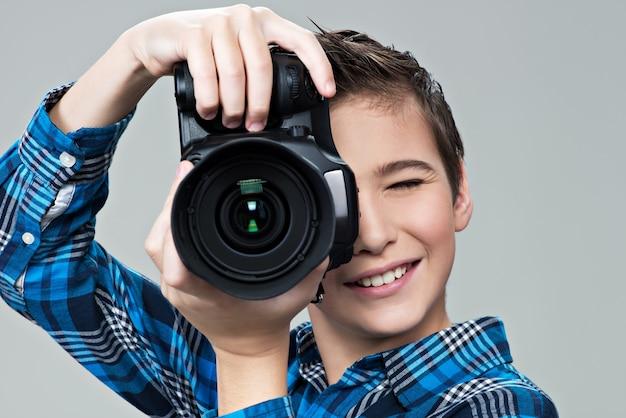 Jongen met fotocamera kijkt in de zoeker
