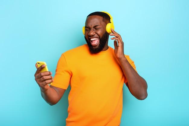 Jongen met gele hoofdtelefoon luistert naar muziek en dansen. emotionele en energetische expressie
