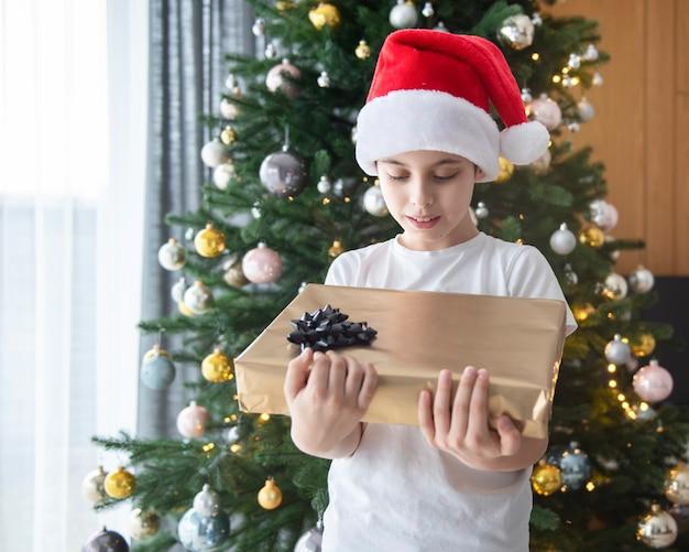 Jongen met geschenken speelt in de buurt van de kerstboom. woonkamer interieur met kerstboom en versieringen. nieuwjaar. cadeaus geven.