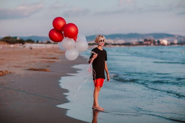 Jongen met gezicht geschilderd als een clown poserend met een bos ballonnen aan het strand