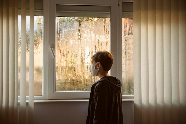 Jongen met gezichtsmasker dat zich naast vensters bevindt