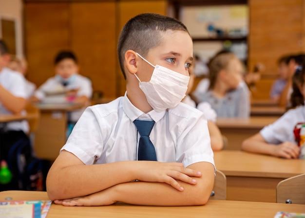 Jongen met gezichtsmasker terug op school na covid-19 quarantaine en lockdown