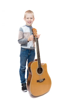 Jongen met gitaar op wit wordt geïsoleerd dat