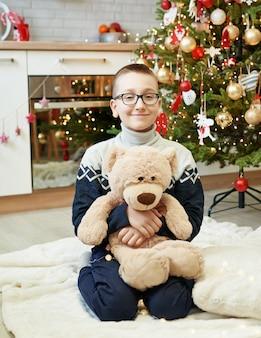 Jongen met glazen en teddybeerzitting dichtbij kerstboom