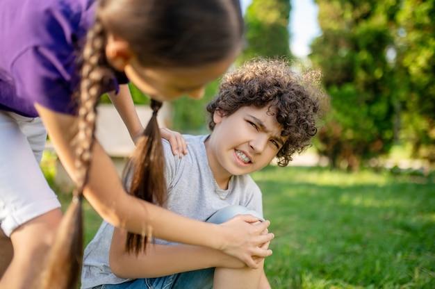 Jongen met grimas die zijn knie en vriendin aanraakt