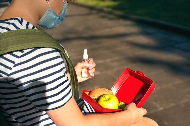 Jongen met handdesinfecterend middel en lunchbox