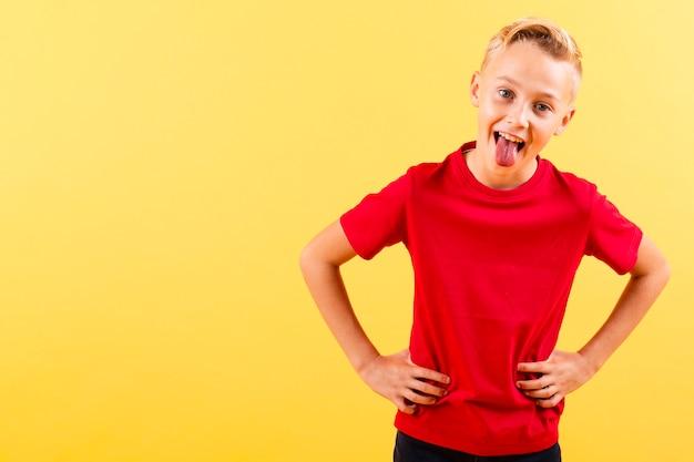 Jongen met handen op taille die tong tonen