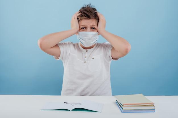 Jongen met het medische masker heeft hoofdpijn met zijn handen op zijn hoofd geïsoleerd op een witte achtergrond zittend...
