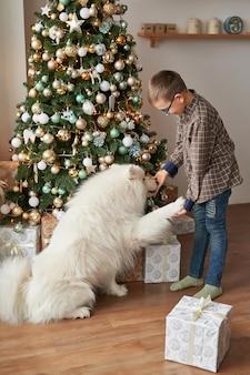 Jongen met hond dichtbij kerstmisboom op kerstmis