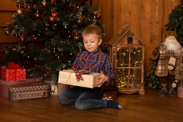 Jongen met kerstcadeautje. schattige kleine jongen met gelukkig nieuwjaar geschenken