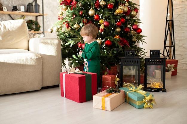Jongen met kerstcadeautjes naast boom