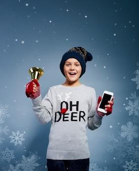 Jongen met kerstmisklok en mobiele telefoon