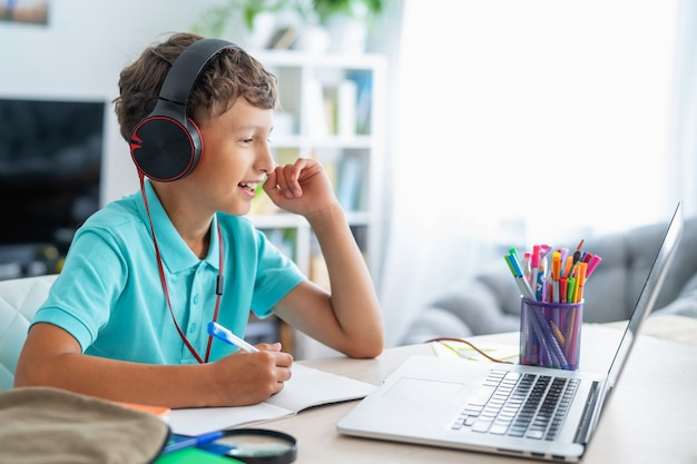 Jongen met koptelefoon met laptop voor huiswerk
