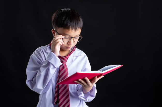 Jongen met kostuum imiteert volwassenen leest