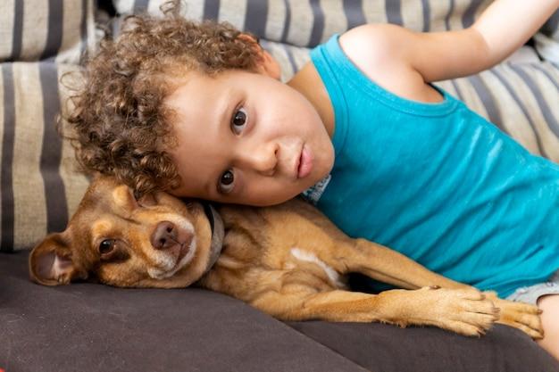 Jongen met krullend haar die met zijn puppy thuis op de bank ligt