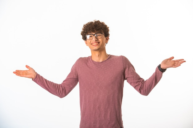 Jongen met krullend haar in een optische bril ziet er succesvol en gelukkig uit.