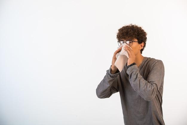 Jongen met krullende haren die optische glazen dragen die zijn neus met weefsel schoonmaken