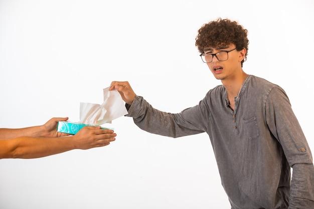 Jongen met krullende haren en in optische glazen die een tissue nemen en recht kijken.