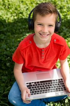 Jongen met laptop en koptelefoon