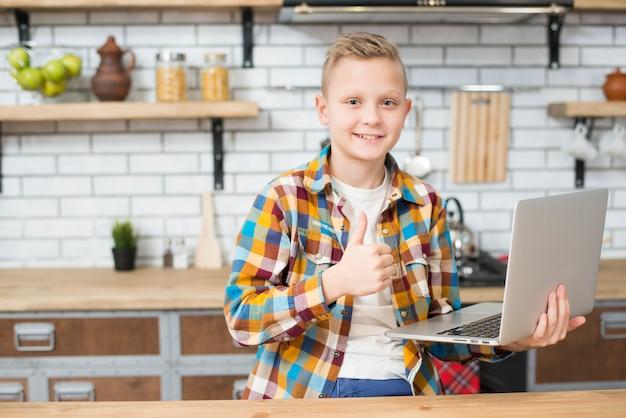 Jongen met laptop in de keuken