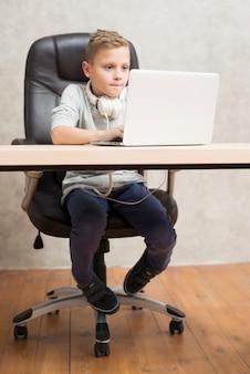 Jongen met laptop op kantoor