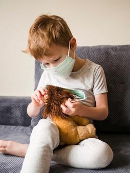 Jongen met masker het spelen met stuk speelgoed thuis