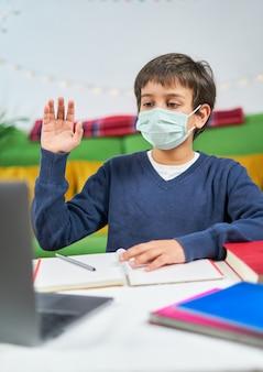 Jongen met masker met een videoconferentie op laptop met leraar vanuit huis, koptelefoon dragen en zwaaien op scherm, vrije ruimte