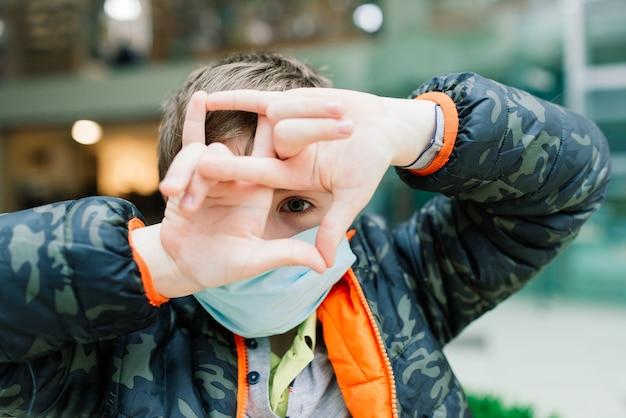 Jongen met medisch gezichtsmasker die diep in gedachten naar buiten kijkt, beschermende maatregelen tegen de verspreiding van covid-19