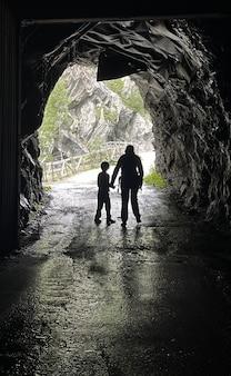 Jongen met moeder in donkere grot in de bergen