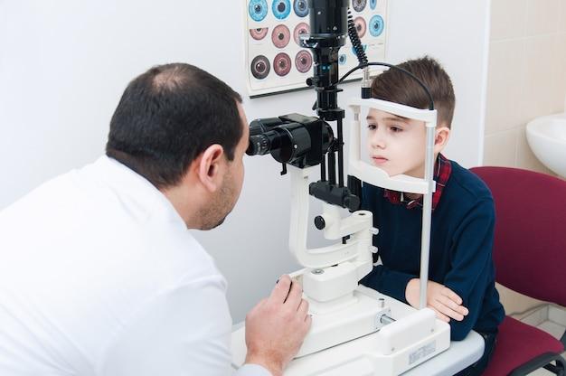 Jongen met moeder op oogonderzoek door oogarts