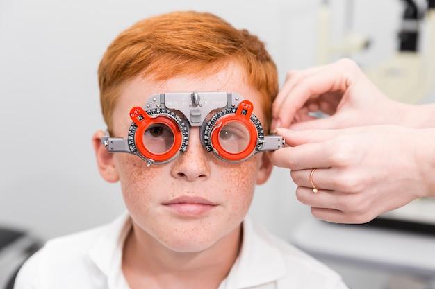 Jongen met optometrist proefkader die zijn ogen in oftalmologische kliniek testen