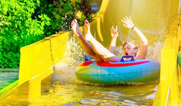 Jongen met plezier op gele waterglijbaan in aquapark. zomervakantie.