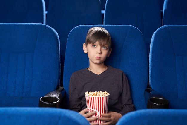 Jongen met poker gezicht kijken naar saaie film in de bioscoop