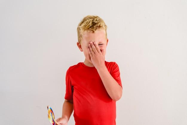 Jongen met rood overhemd op witte achtergrond die een een lolly kleurrijke pret en het lachen eet