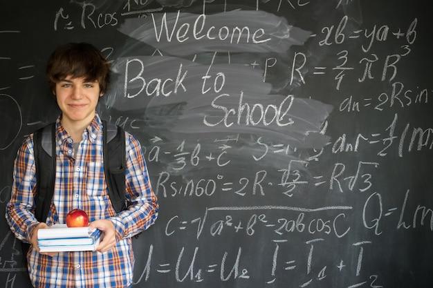 Jongen met rugzak, boeken en appel met terug naar school en ingewikkelde wiskundige formules op zwarte bord