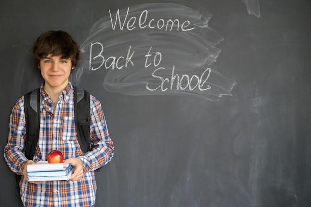 Jongen met rugzak, boeken en appel met terug naar school op zwart bord