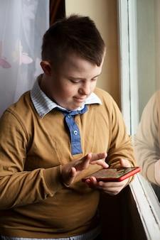 Jongen met smartphone van het syndroom van down