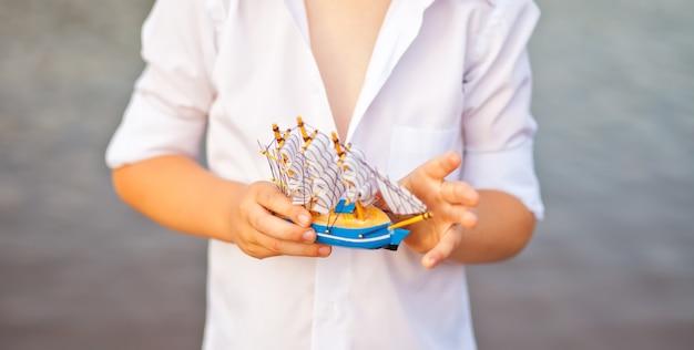 Jongen met speelgoedboot, model van het schip.