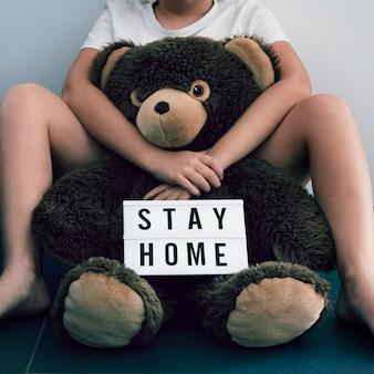 Jongen met teddybeer zittend op de vloer