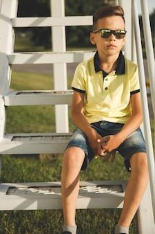 Jongen met trendy kapsel op de trap met een zonnebril