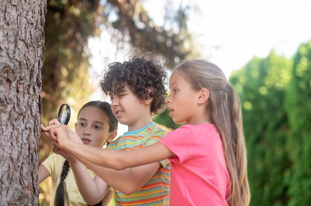 Jongen met vergrootglas en twee meisjes