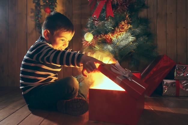 Jongen met verrast gezicht die magische kerstcadeaudoos opent met rook in houten kamer